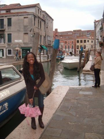 Nneya standing in front of a riverboat with an umbrella, on a rainy day