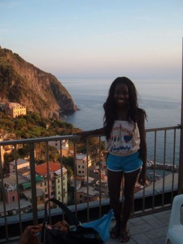 Nneya standing on a balcony in front of the ocean