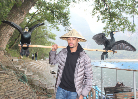 Terrence in a hat with a bar across his shoulders.  On the ends of the bar, sit birds with their wings spread wide.