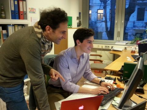 Will and a colleague working on a computer in an office