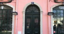 A pastel pink building facade with an arched doorway and two windows in Lisbon, Portugal