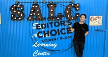 student in front of SALC sign on blue wall with editor's choice logo