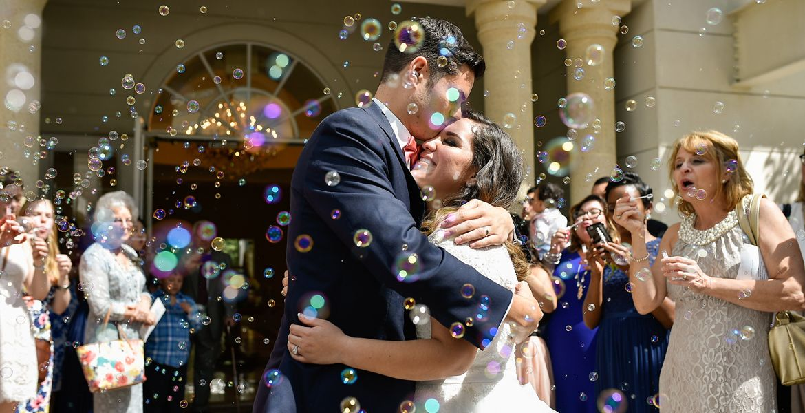 Justin and Monica at their wedding surrounded by guests blowing bubbles