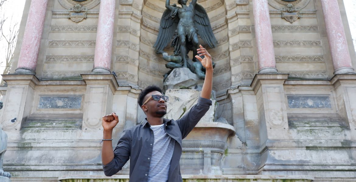 student posing in front of st michael statue in paris