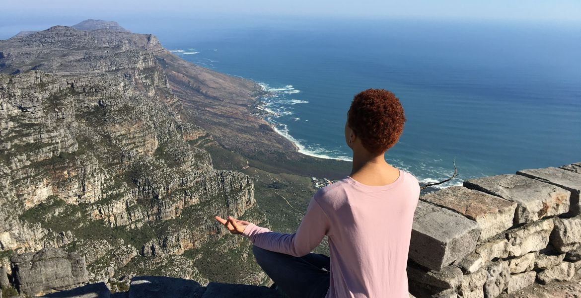 a student sits on a cliff near the ocean