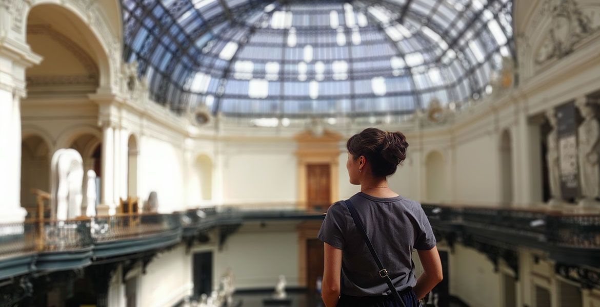 A student looks over a balcony in a museum
