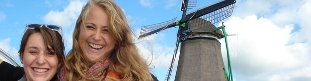 Students pose in front of a classic windmill in Amsterdam