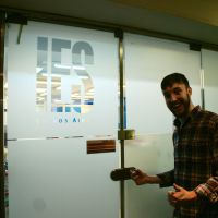 student smiling in front of frosted IES Abroad logo on door