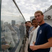 four students smiling looking over the railing at the view