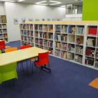 A bright room with tables, chairs, and bookshelves inside the Center.