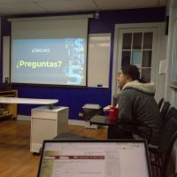 student sitting in front of presentation with Preguntas on screen