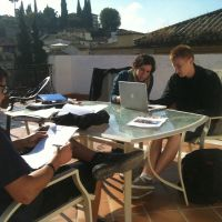 three student studying on a sunny day on terrace