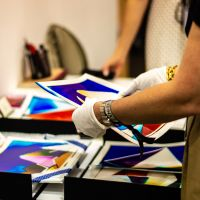 Delicate photographic prints being handled with care by an exhibitor in gloves.