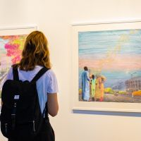 """A guest admires a mixed media piece by Joana Choumali in the exhibit """"Woven Matters."""""""