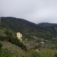 Yellow house tucked within the hills of Corniglia