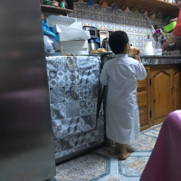 A young boy scouts out the kitchen, too impatient to wait for the late dinner