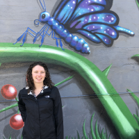 Skylar standing next to a mural with a butterfly