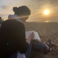 A person sitting on the beach, watching the sunset while journaling.