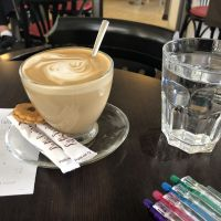 A coffee, water, and set of pens sitting in a cafe table