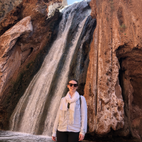 A person standing in front of a waterfall.