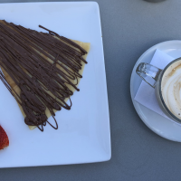 A nutella crepe next to a coffee on a cafe table.