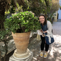 A person standing next to a potted house plant