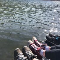 Three people hanging their feet over a lake