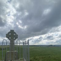 A view of a stone cross, with rolling clouds obscuring the sun