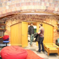 Two men standing in rounded doorway in student lounge area