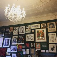 Room with framed photos covering wall and chandelier hanging from ceiling