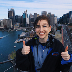 student standing on bridge overlooking sydney with two thumbs up