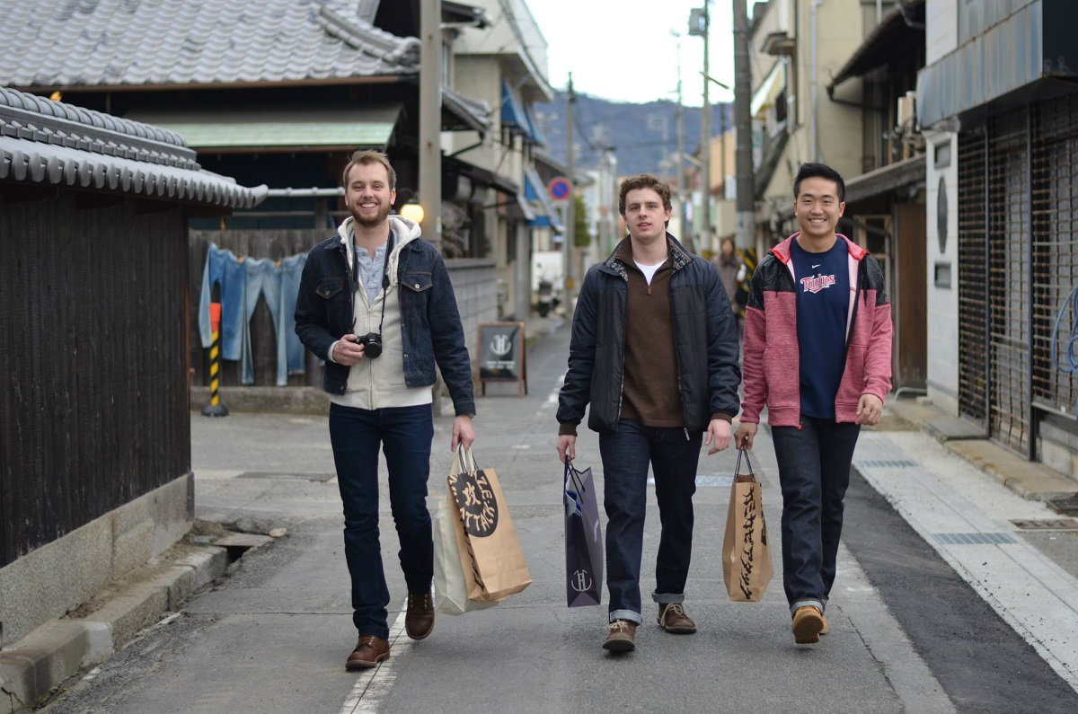 three male students with shopping bags walk down a street in Tokyo