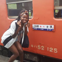 student posing by train in Japan